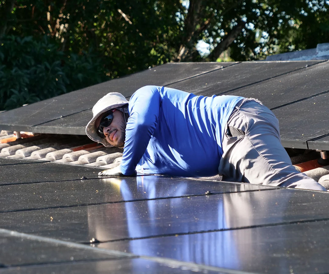 Experienced solar panel installer working on roof